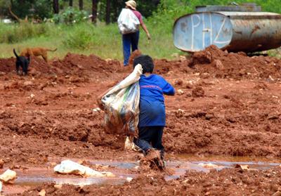 Criança saindo de lixão após coleta de recicláveis - Foto: Marcello Casal Jr./Agência Brasil via Wikimedia Commons