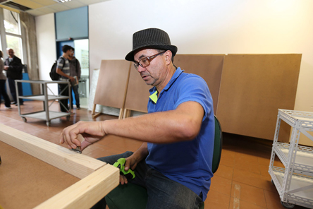 José Carlos Batista monta os porta banners com sucata de madeira - Foto: Marcos Santos/USP Imagens