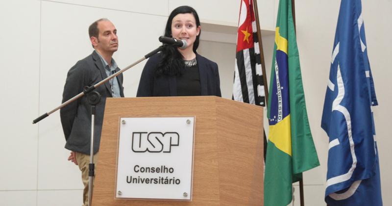 """A pesquisadora Angela Castoldi (e, ao fundo, seu orientador, Niels Olsen Saraiva Câmara) durante apresentação resumida de sua tese intitulada """"MyD88: um modulador do perfil inflamatório e metabólico na obesidade experimental"""", premiada na Grande Área Ciências Biológicas - Foto: Ernani Coimbra"""