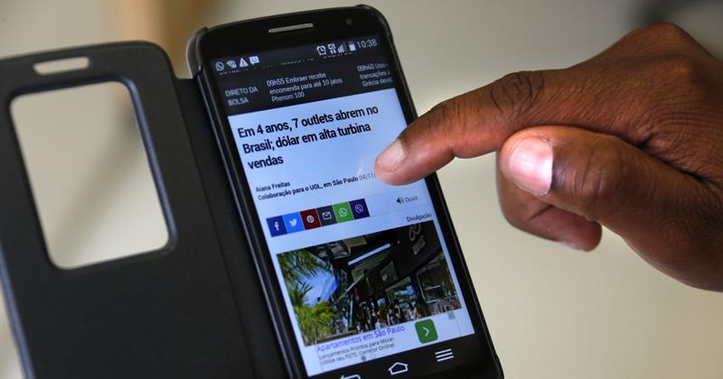 Usuário lendo notícias no celular via internet - Foto: Cecília Bastos/USP Imagens