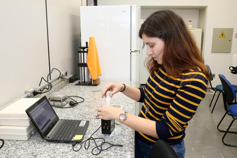 Pesquisadora Tatiana Cardoso D'Amato injeta líquido em amostra de folha no medidor de ângulo de contato - Foto: Marcos Santos/USP Imagens