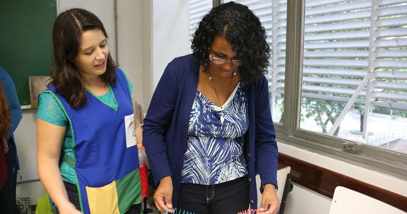 Daiana Barone (aluna do IF) orientando a professora de Portugues Cassia Caetano no 13º Encontro USP - Escola realizado no Instituto de Física . Foto: Cecília Bastos/USP Imagens