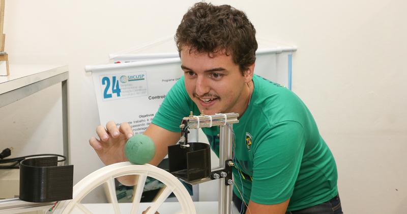 Fernando dos Santos Barbosa demonstra o dispositivo Bola e Roda - Foto: Marcos Santos-USP Imagens