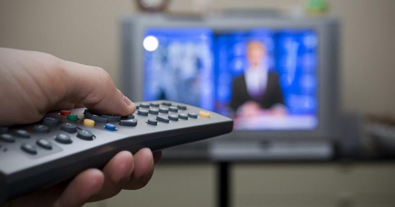 Em primeiro plano, uma pessoa aponta um controle remoto para uma TV que está ao fundo. A imagem ao fundo está borrada, impedindo identificar o programa passando na televisão.