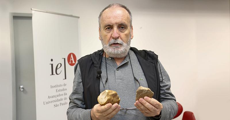 Professor Walter Neves mostra antigos artefatos de pedra lascada em suas mãos
